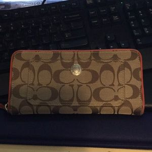 Coach beige w/orange trim zip around full wallet